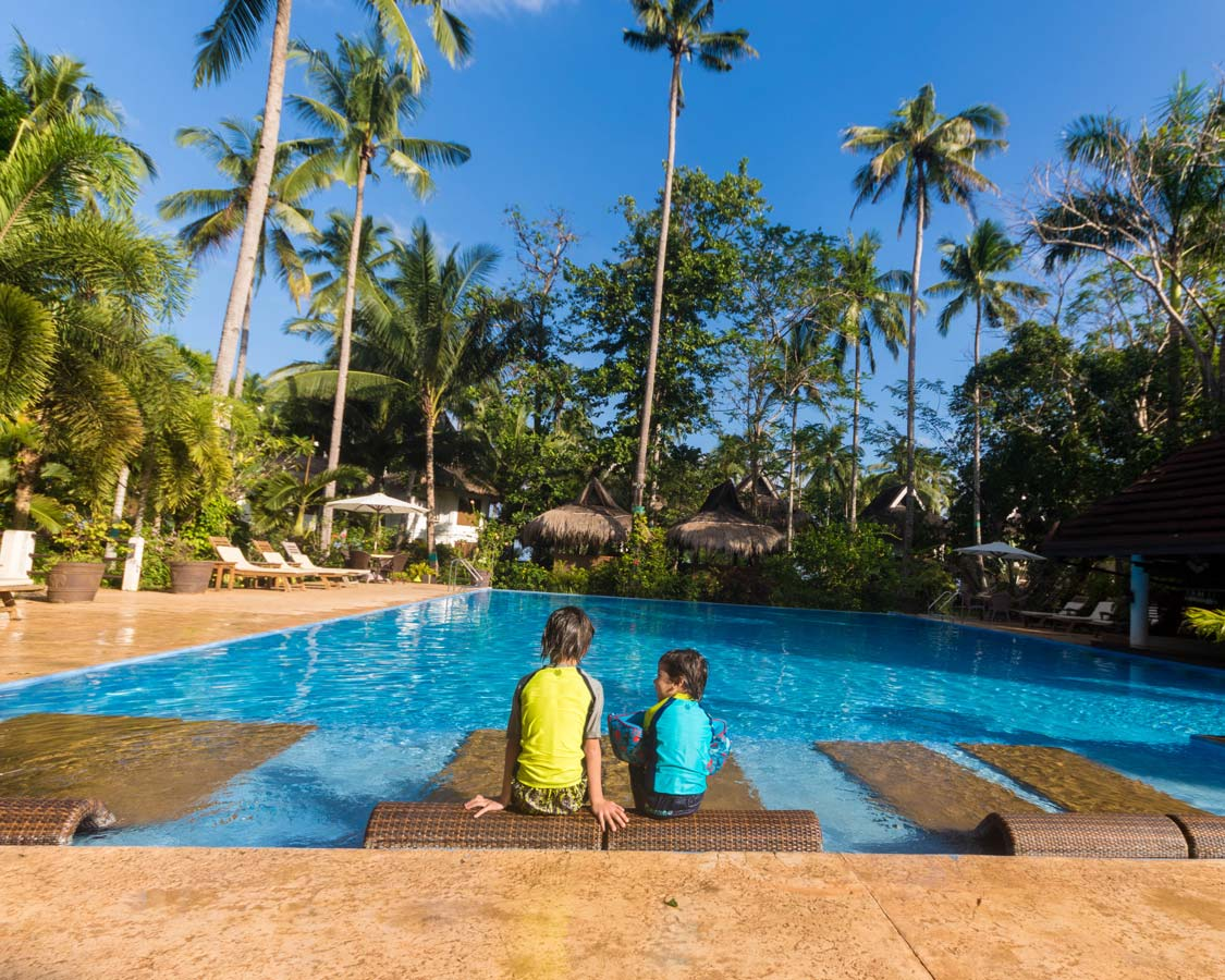 Two boys relax in a pool at Daluyon Beach and Mountain Resort Puerto Princesa Philippines