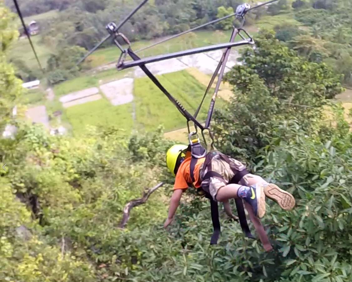 Young boy riding zipline at Ugong Rock in Puerto Princesa Philippines