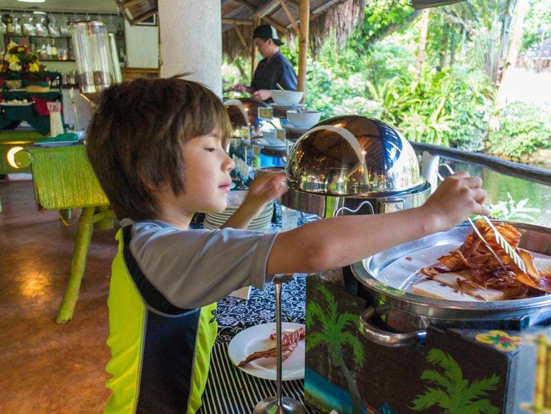 Young boy serves bacon at Daluyon breakfast buffet in Puerto Princesa Philippines