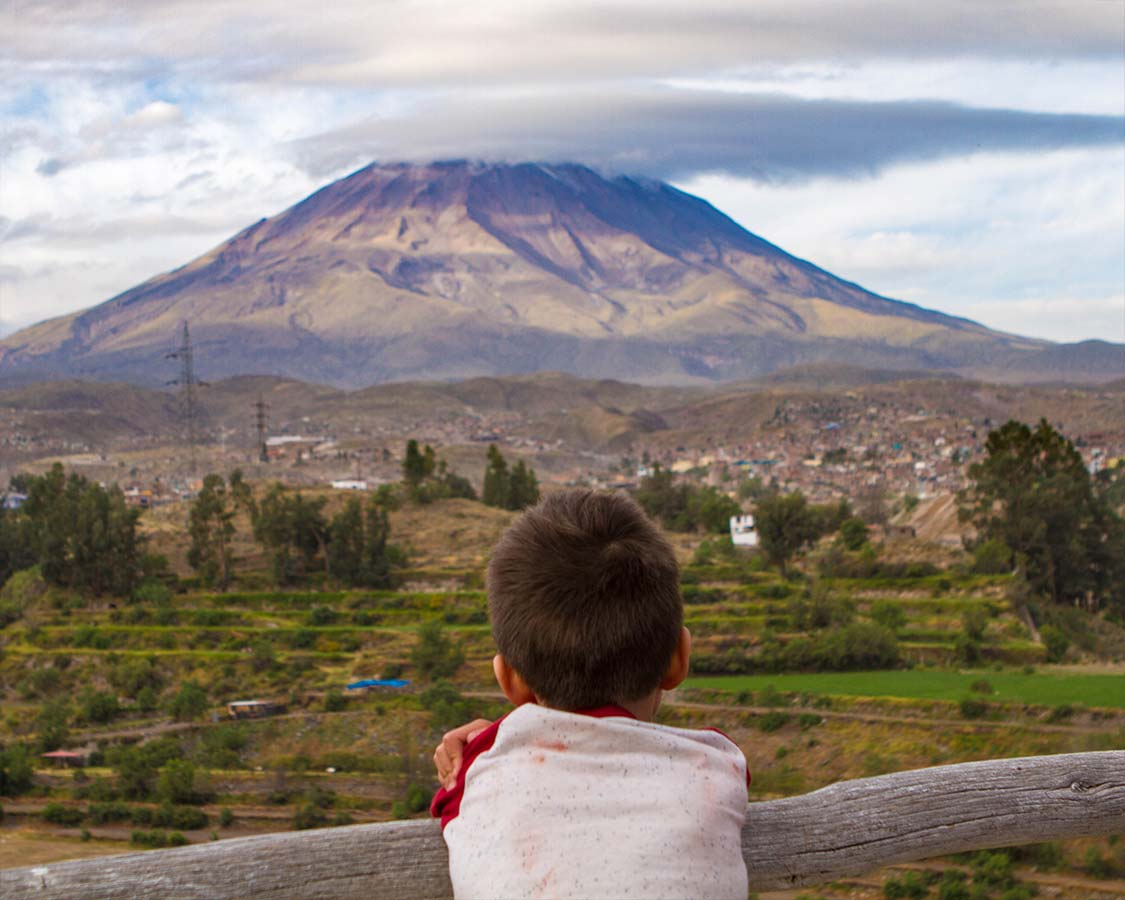 Boy looking at a volcano in Arequipa Peru
