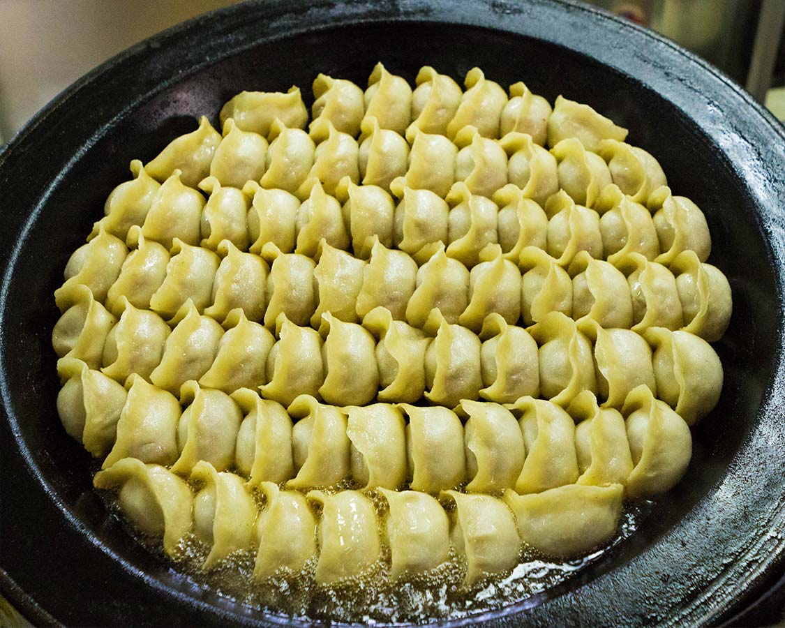 Chinese soup dumplings being fried in Shanghai food tour