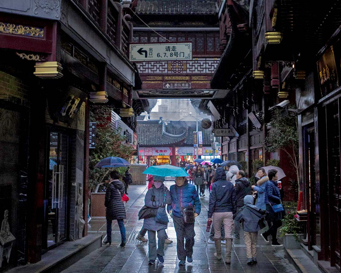Shoppers in old town Shanghai on a rainy day