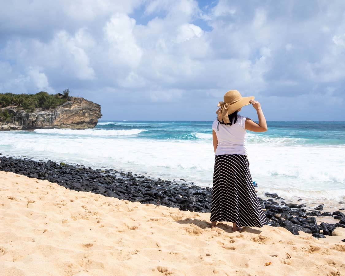 Kauai Shipwreck Beach with woman holding hat against the wind things to do in Kauai with kids