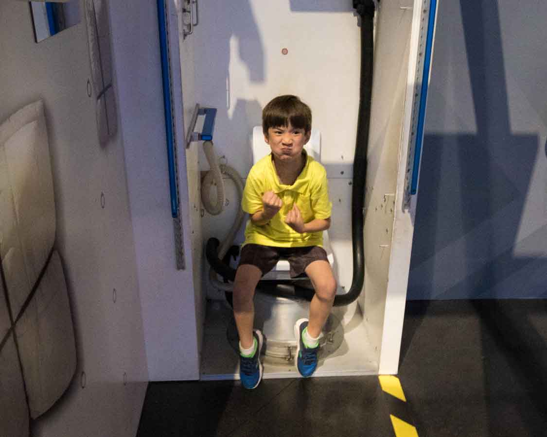 Testing astronaut toilet at Kennedy Space Center for families