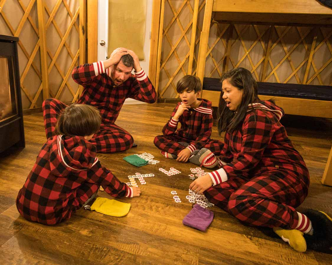 Family playing board games in a MacGregor Point Yurt