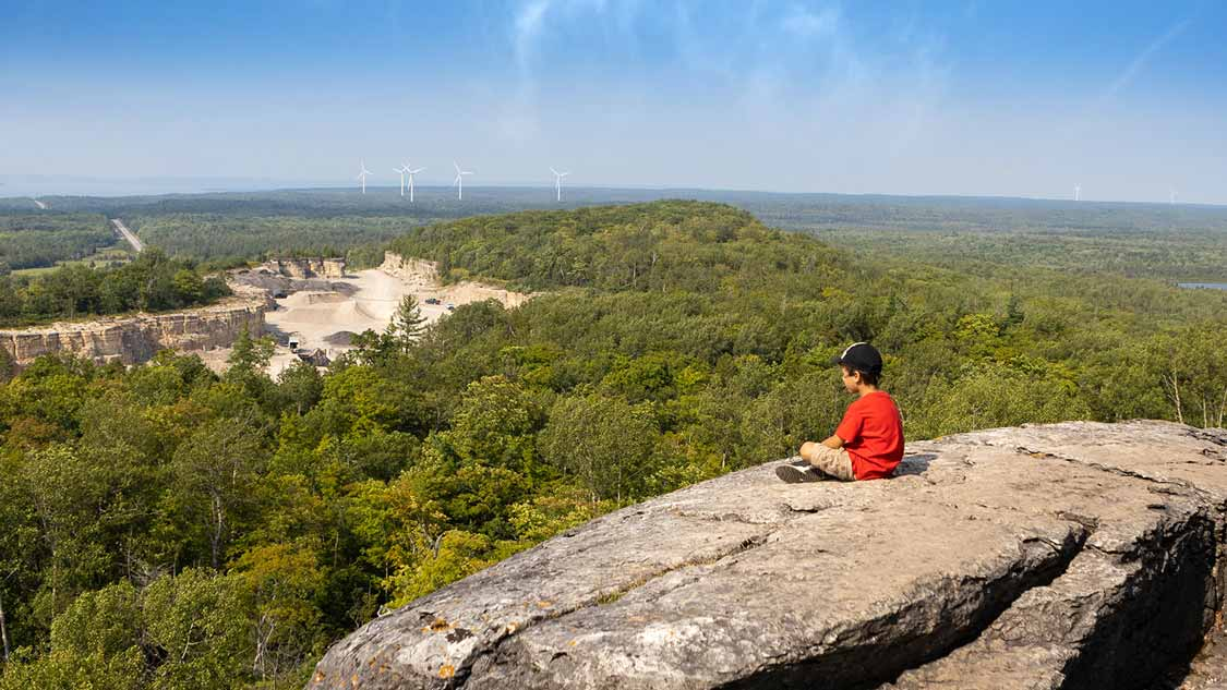 Young boy sitting at the Cup and Saucer Trail Overlook