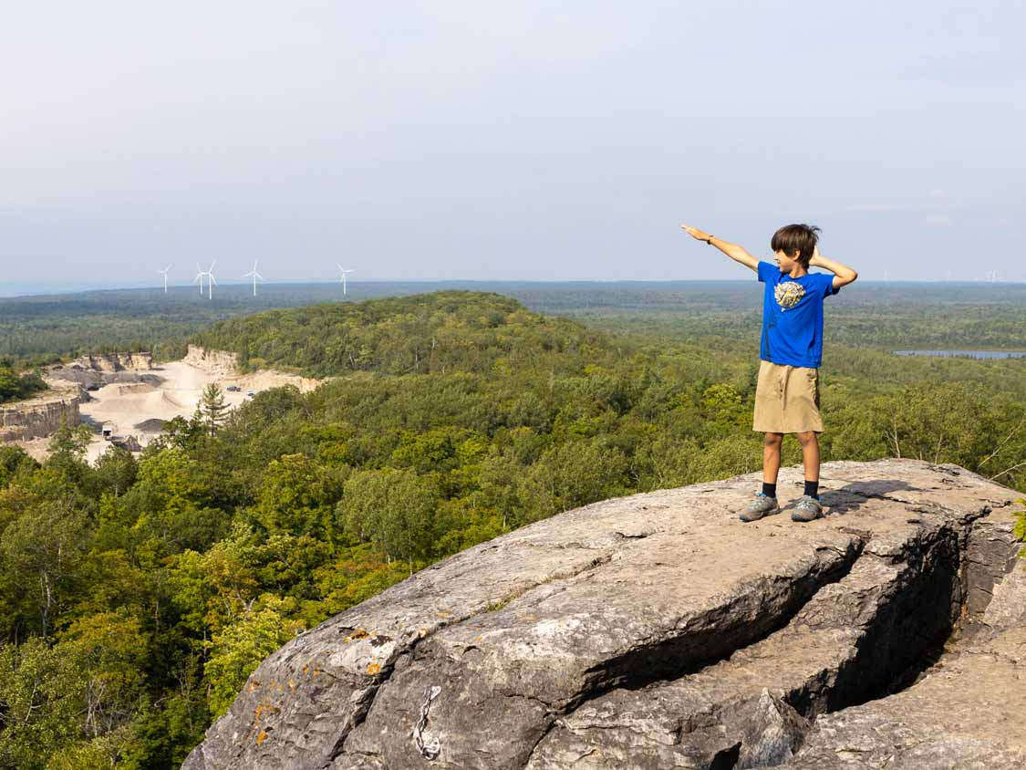 Boy poses after climbing the Manitoulin Cup and Saucer Trail