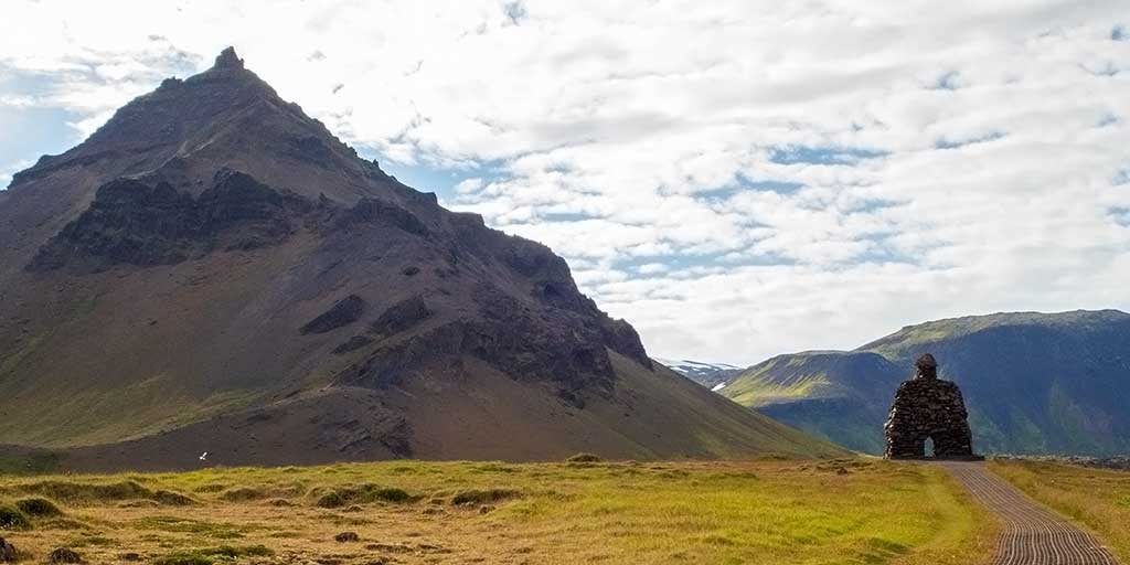 Statue of a giant beneath a cone mountain in Iceland