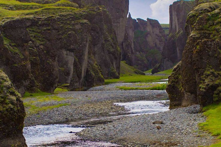 Beautiful canyon in Iceland with hills topped with green grass and a small river winding down the middle