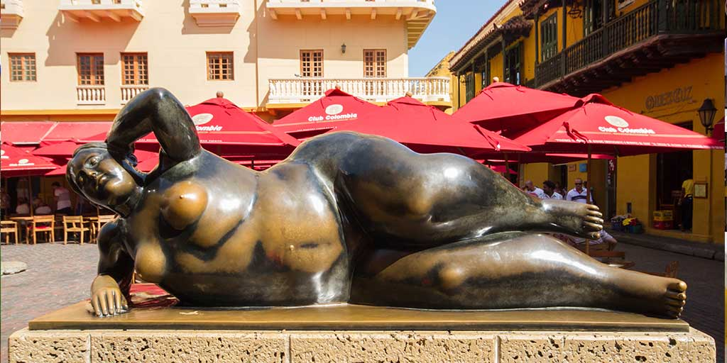 Statue of a woman lying down in a town square in Cartagena, Colombia
