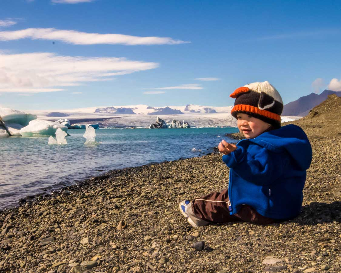 A young boy wearing a penguin hat sits at the edge of a glacier filled lagoon in Iceland for kids