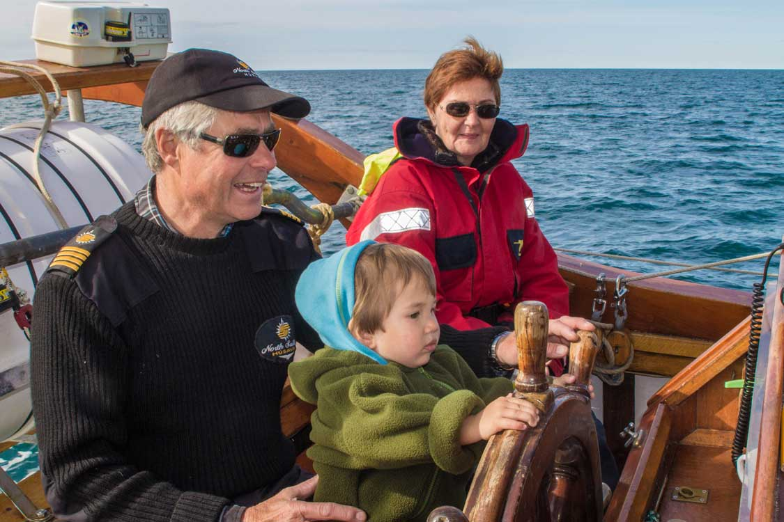 A young boy at the wheel of a schooner on a whale watching tour in Iceland with kids