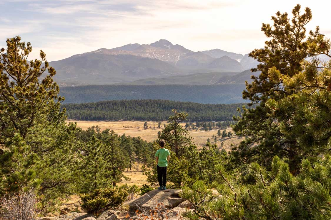 Boy looking out over fields and mountains at Rocky Mountain National Park in Colorado
