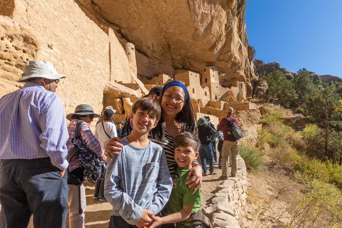 Mother and two sons smile in front of adobe cliffside dwellings in Mesa Verde National Park in Colorado