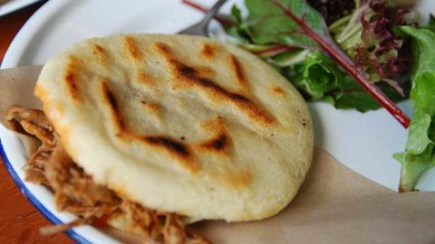 Colombian arepa stuffed with meet and cheese served with a salad