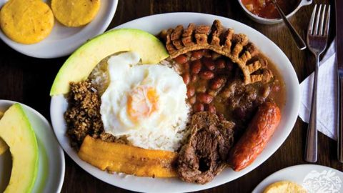 beans and rice topped with an egg, pork belly, chorizo, and served with sliced avocado