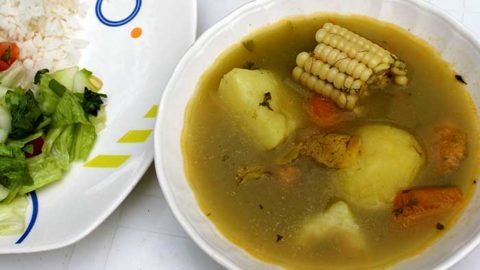 Soup with chicken, potato, and yucca served in a white bowl next to a salad