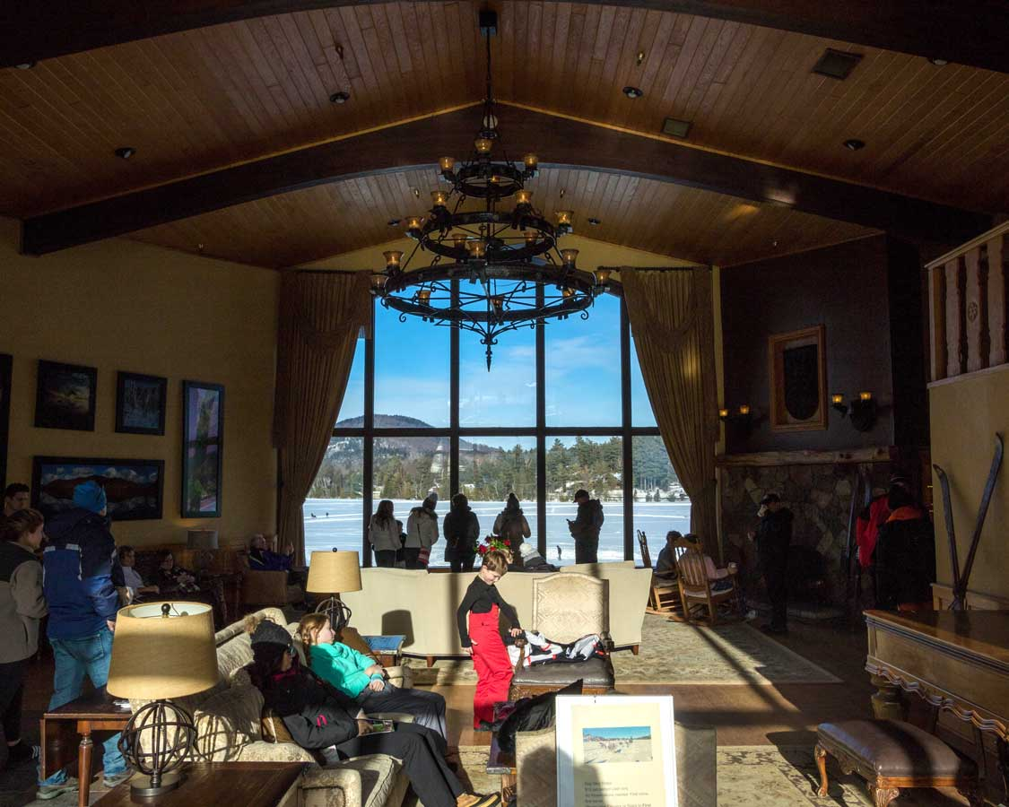 The luxurious interior of the Golden Arrow Hotel lobby looking out over Mirror Lake in Lake Placid