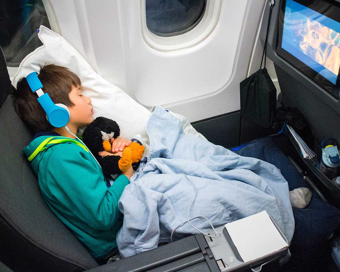 Young boy with a penguin stuffy wearing headphones while sleeping on a plane