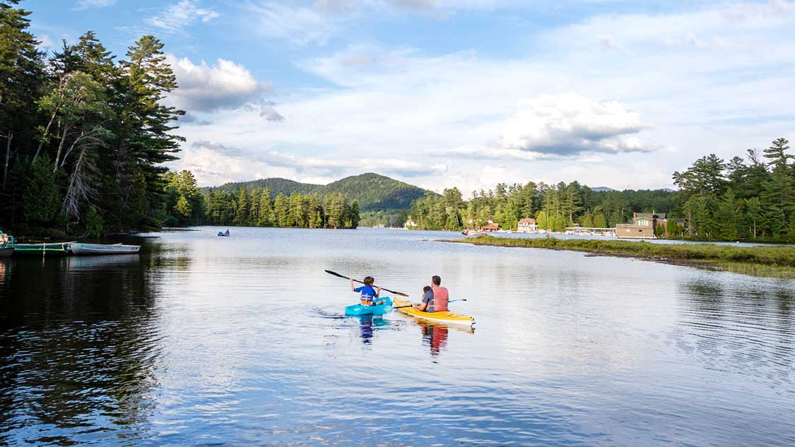A father kayaks with his two children on Mirror Lake in Lake Placid New York