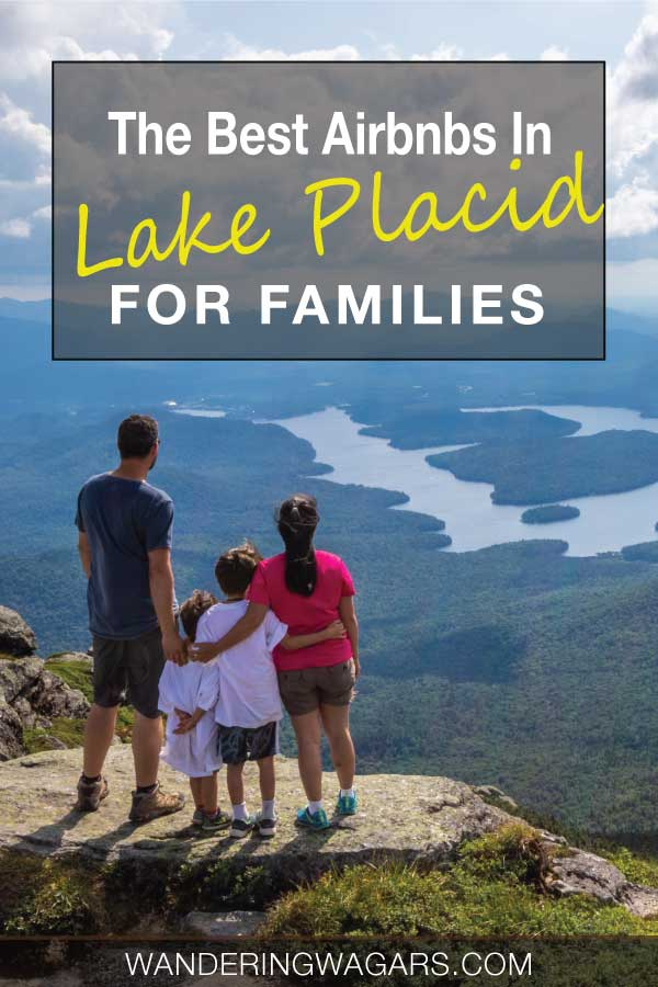 A family standing on top of a mountain looking out over a shimmering lake.
