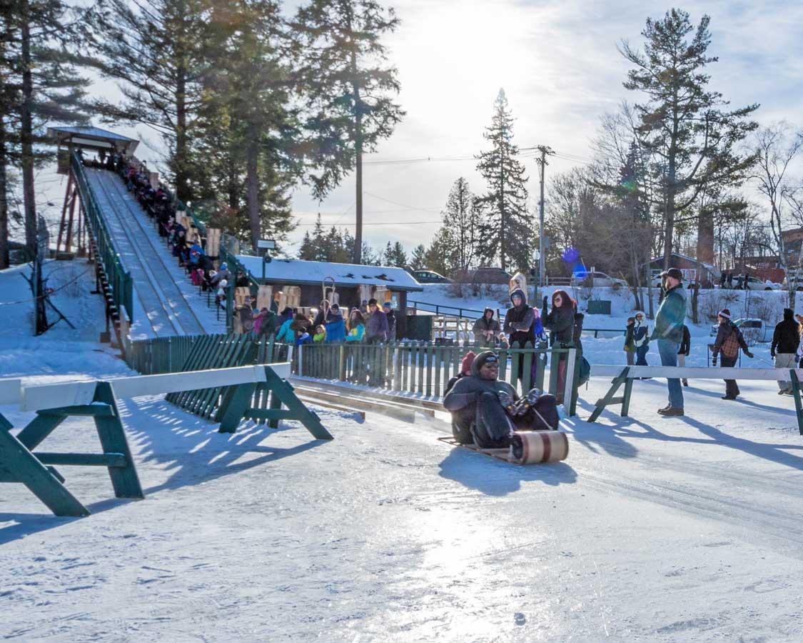 Crowds watch tobogganers slide across the lake in Lake Placid