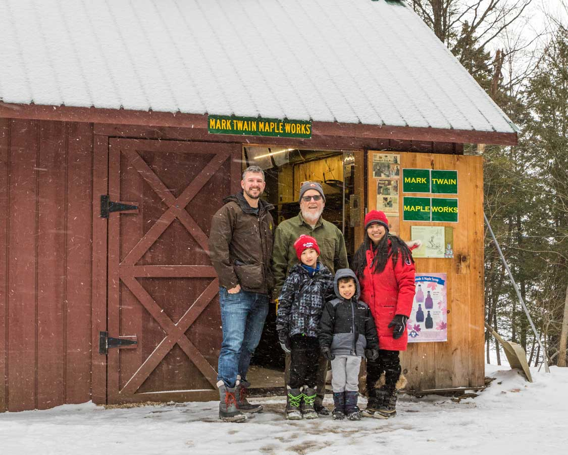 A family poses with the owner of a maple syrup farm near Lake Placid New York