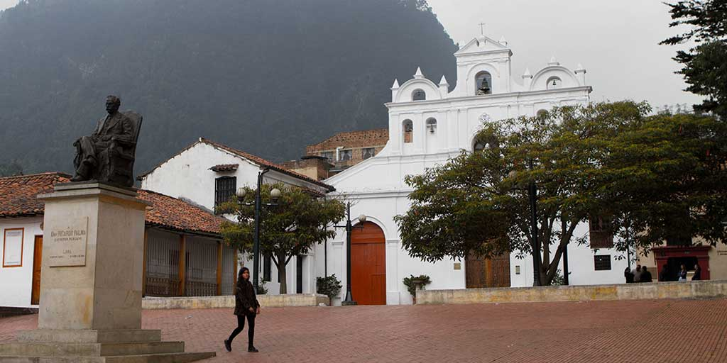 A woman walks past a bell near a white church in Bogota Colombia