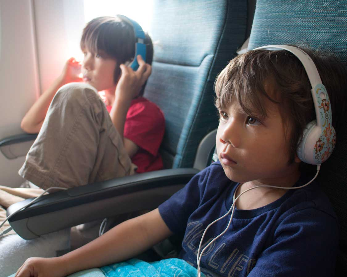two boys wearing headphones whle watching movies on an airplane
