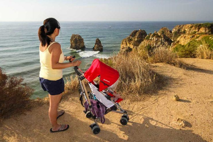 Woman pushing the best travel stroller along oceanside cliffs in Portugal