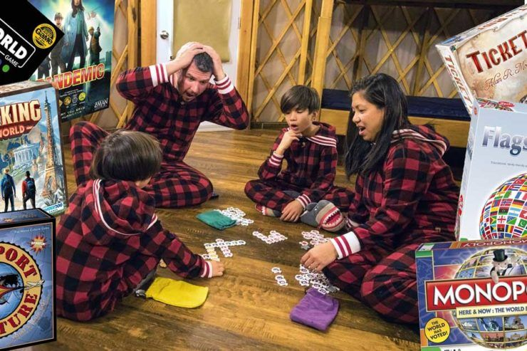Mixed race family playing travel-themed board games in a cabin
