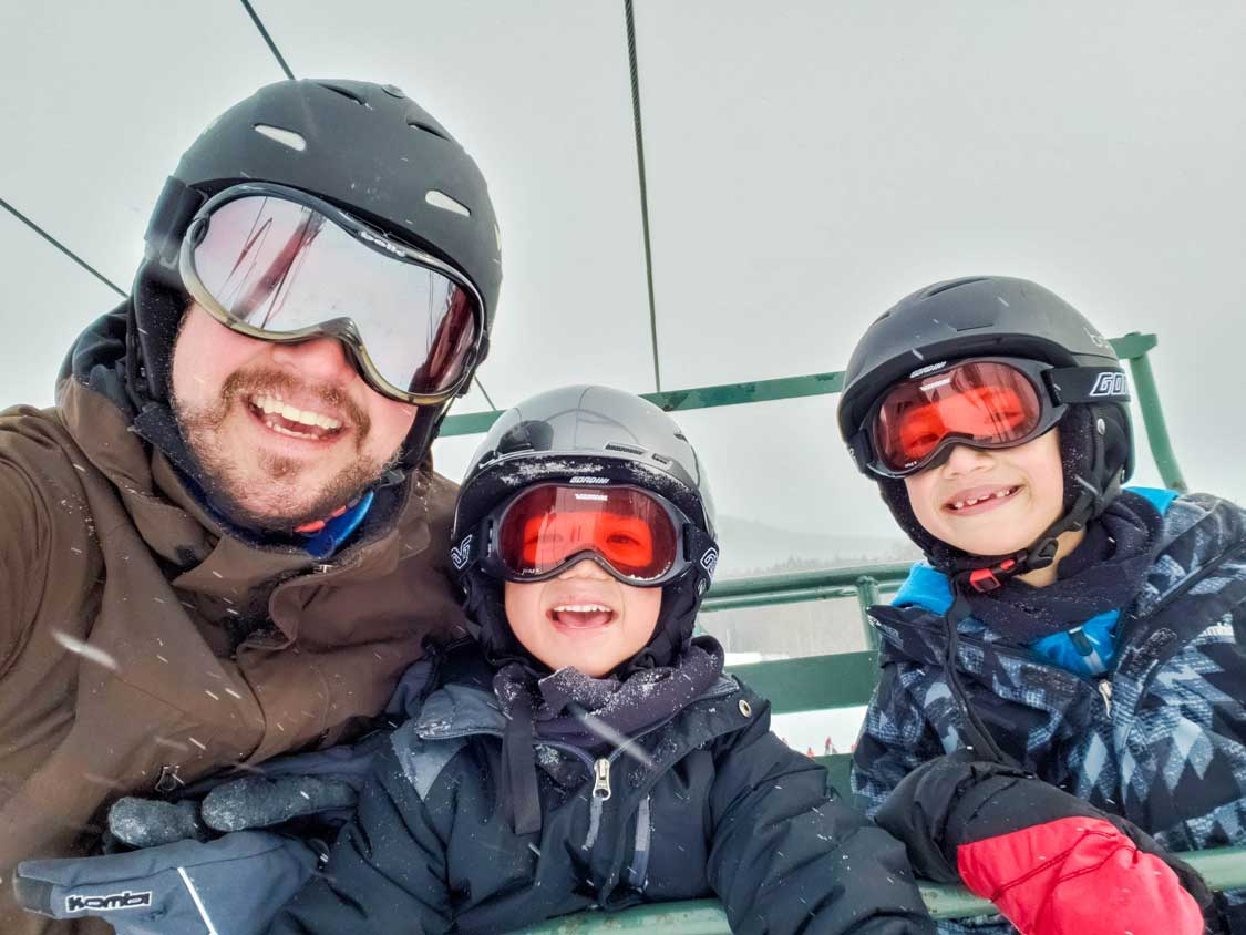 Father and two kids on a ski lift in the Finger Lakes of New York State