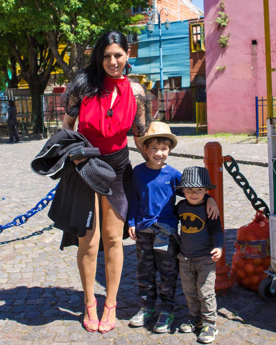 Two young boys pose with a tango dancer in La Boca Buenos Aires with children