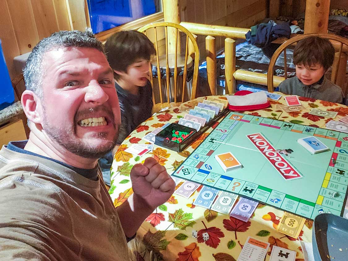 scowling father losing at board game to his children
