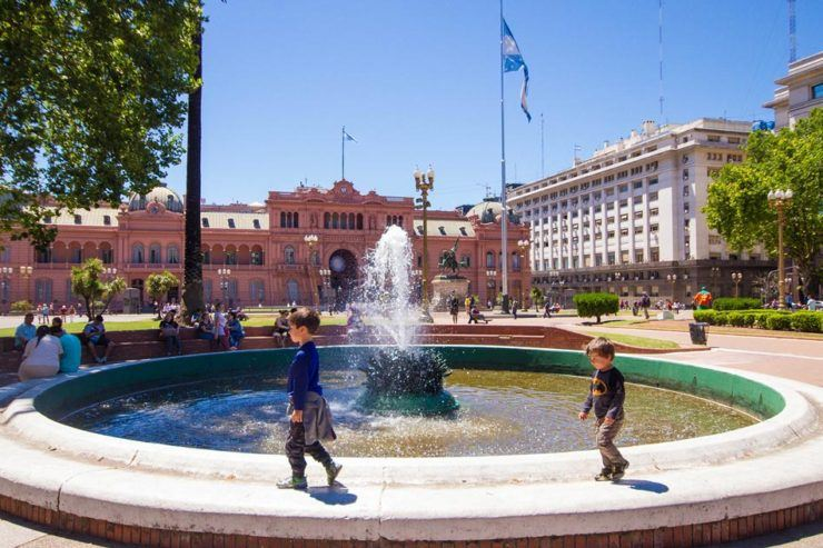 Two young boys walking around a fountain in Paza de Mayo in Buenos Aires with kids