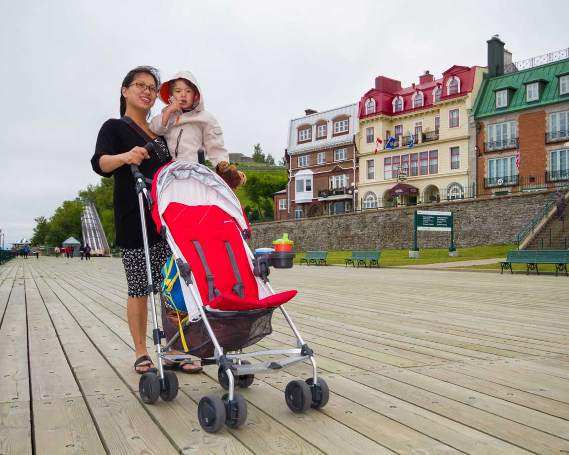 Woman holding a baby while pushing a compact stroller in Quebec City