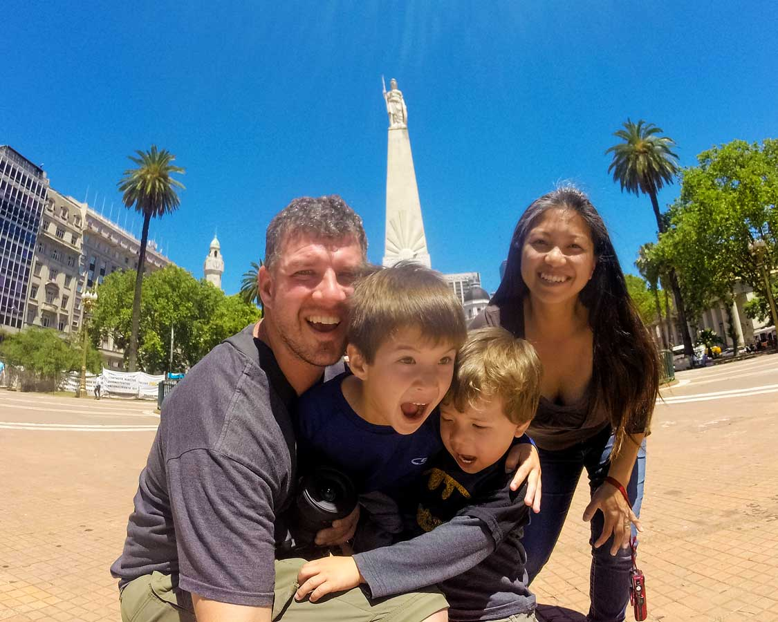 A young family making funny faces at the camera in a plaza in central Buenos Aires