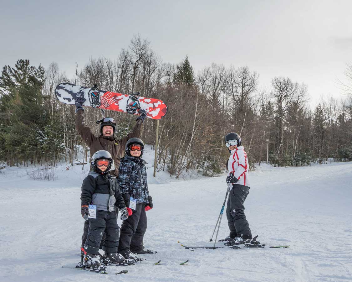 A family laughing while posing for a ski photo in New York State