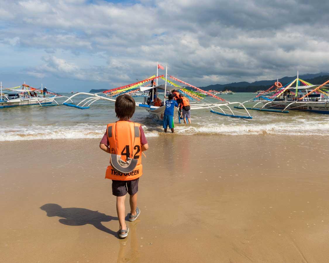 Boy boarding a paraw at the Puerto Princesa Subteranean River