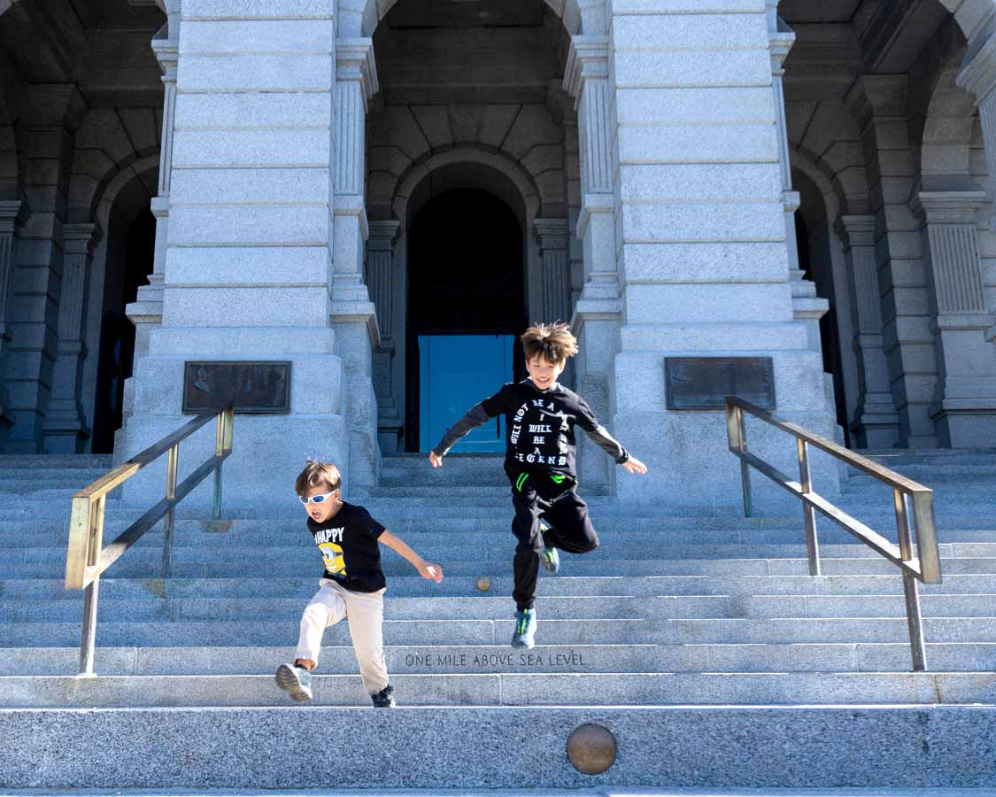 Children jumping from the mile high step at the Colorado Capitol Building in Denver with kids
