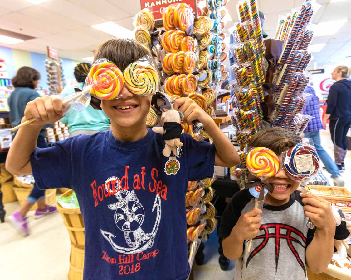 Children holding lollipops over their eyes at Hammond's Candy Factory