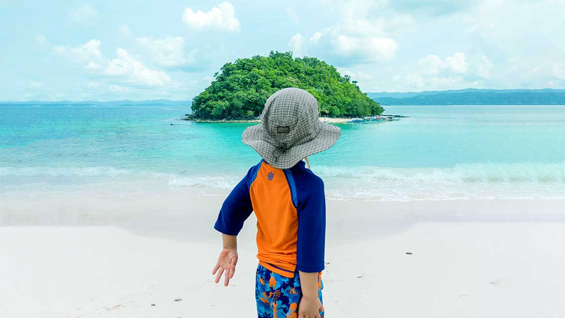 Boy looking at an island from a white sand beach in the Philippines with kids
