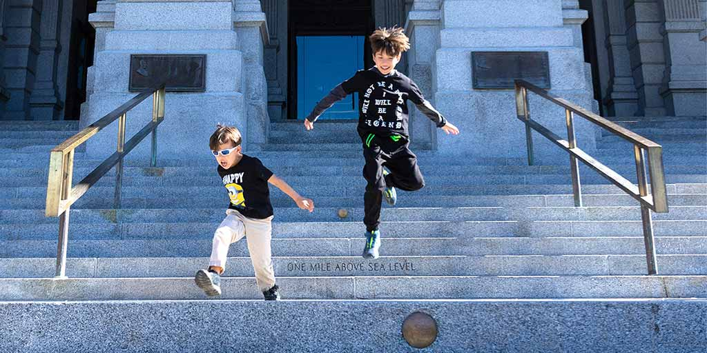 Two boys jumping from the mile-high step searching for things to do in Denver with kids