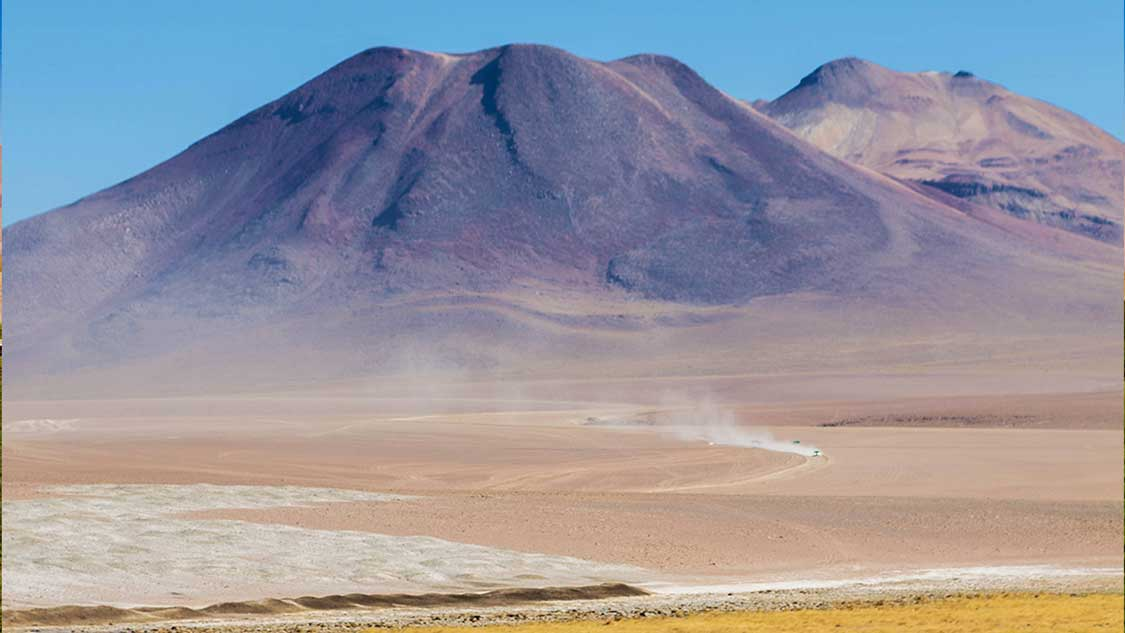Car driving to San Pedro de Atacama beneath mountains