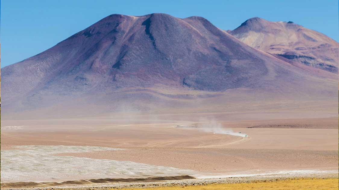 Car driving to San Pedro de Atacama beneath mountains
