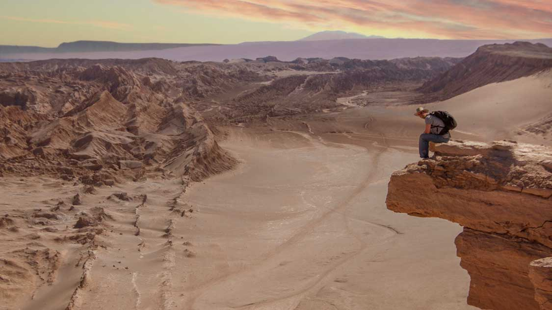 Man sitting on a rock ledge of the Valle de la Muerta in the Atacama Desert