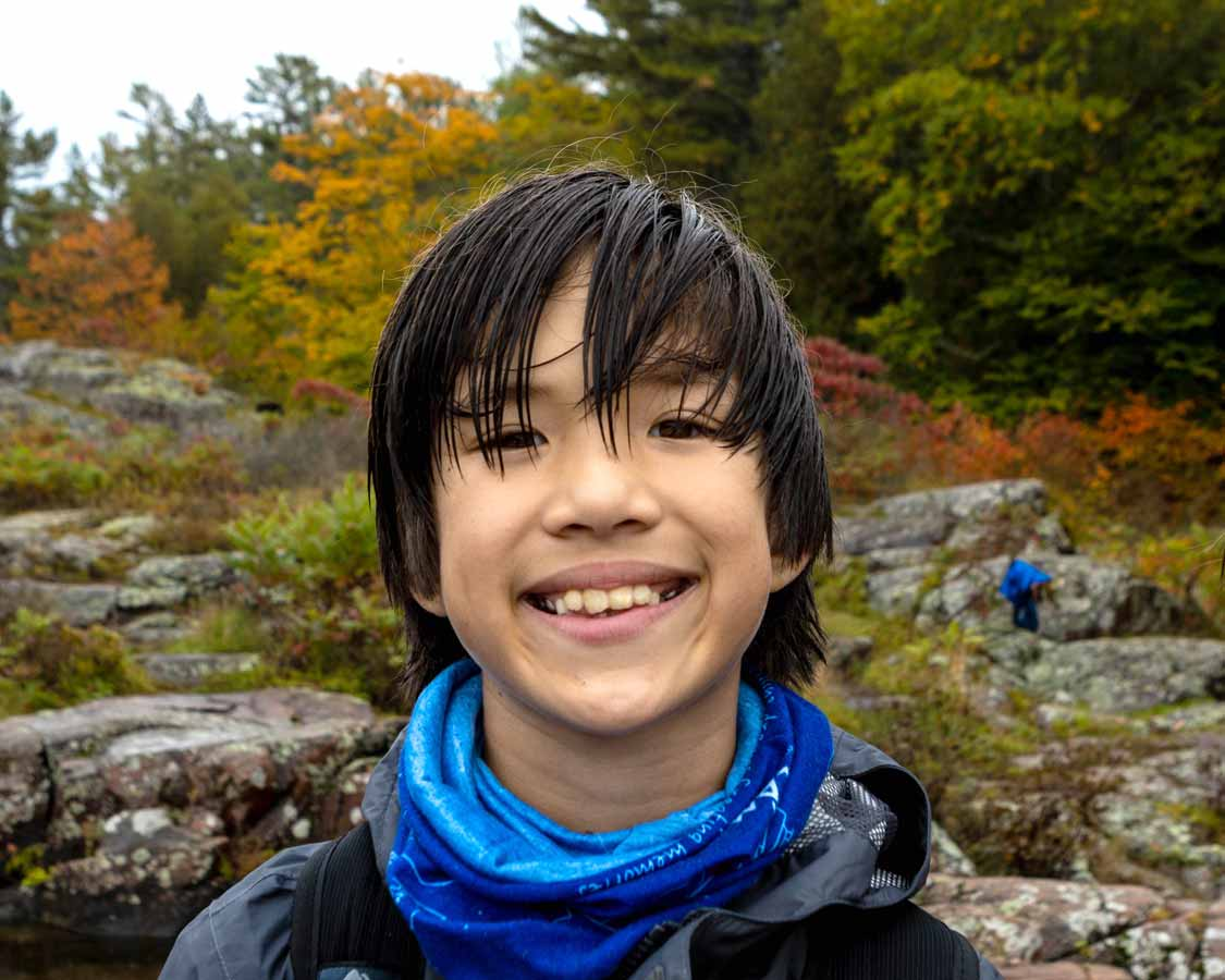 Boy hiking in the rain at French River Provincial Park