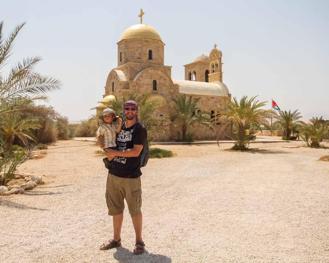 A boy and his son stand by a church at Bethany Beyond the Jordan