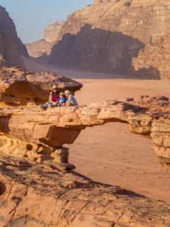 Family climbing rock arches in Wadi Rum as they explore things to do in Jordan