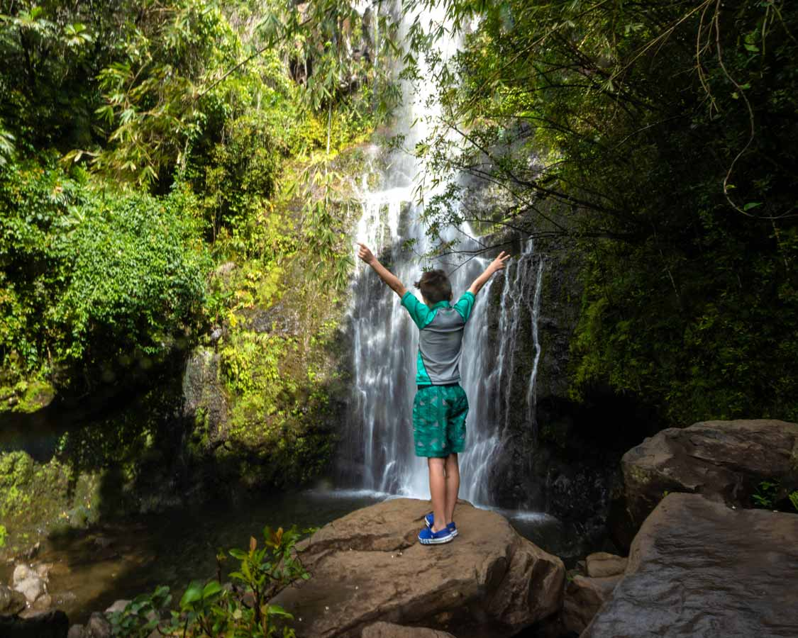 Where to stay in East Maui boy standing by a waterfall